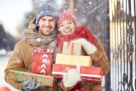 Young couple with Christmas presents looking at camera
