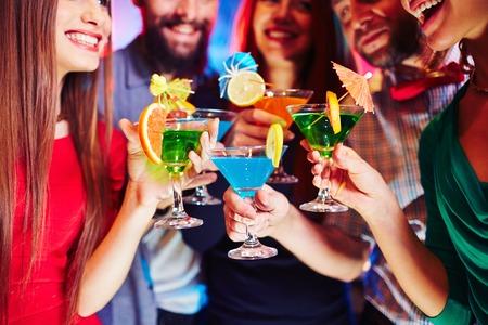 cocteles: Amigos alegres que sostienen los vidrios de martini con cócteles Foto de archivo
