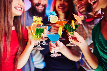 clubber: Cheerful friends holding martini glasses with cocktails
