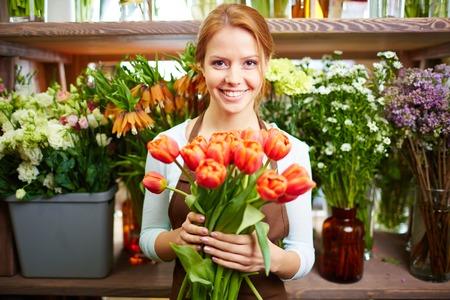 彼女の店でカメラを見て新鮮な赤いチューリップと幸せな女 写真素材