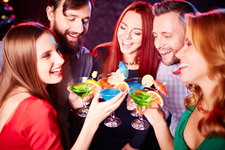 booze: Happy young friends with cocktails having booze Stock Photo