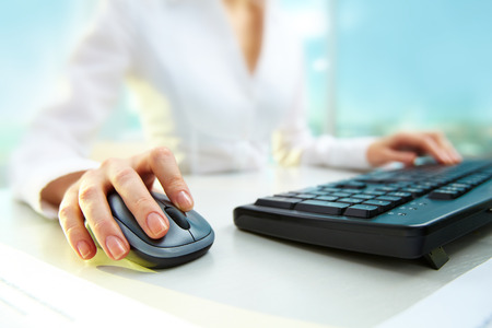 mouse: Businesswoman pushing key of a computer mouse while typing