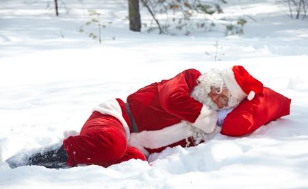 Santa Claus sleeping in snowdrift in winter forest photo