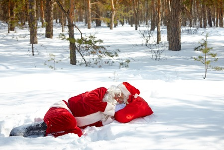 Tired Santa Claus sleeping in snowdrift photo