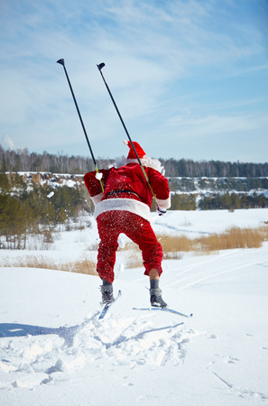 Santa Claus skiing in winter forest photo