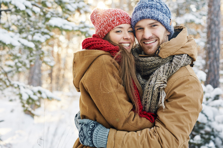 Embracing dates in winterwear looking at camera in natural environment
