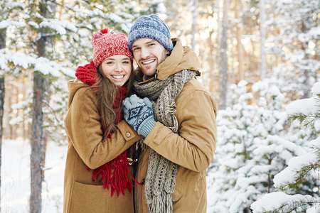 романтика: Охватывая пара, глядя на камеру с улыбкой в зимний парк Фото со стока