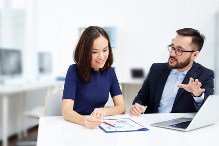 executive woman: Two employees discussing document at meeting