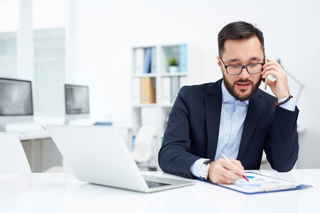office man: Young Asian businessman speaking on the phone in office Stock Photo