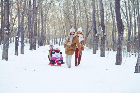 persona feliz: Feliz el hombre que monta los niños en el trineo en el parque de invierno Foto de archivo