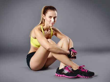 activewear: Young fit woman in active-wear sitting on the floor and looking at camera
