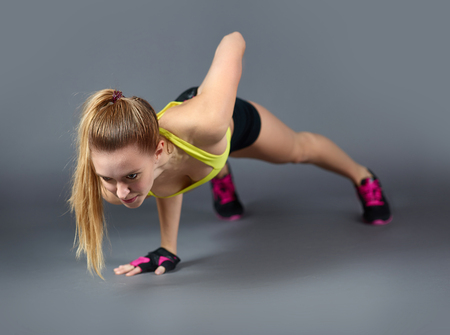 physical fitness: Pretty young female practicing exercise for arms Stock Photo