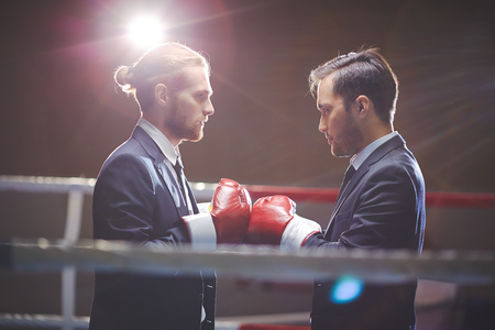 conflicts: Two young businessmen boxing on boxing ring