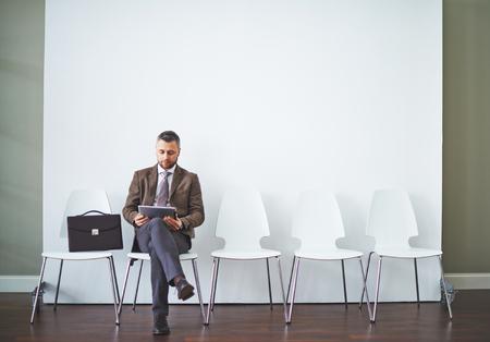 persona sentada: Hombre de negocios con touchpad sentado en la silla y esperando