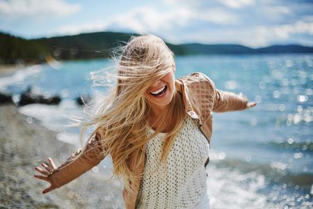 Jonge blonde lachend in de buurt van de kust Stockfoto