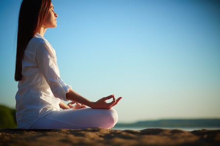 Woman sitting in lotus position and meditating Standard-Bild