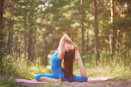 plasticity: Young woman stretching in yoga position in the forest