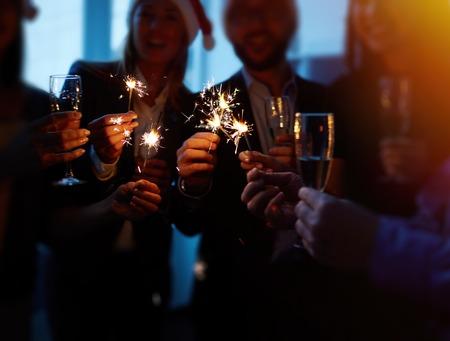 Groupe de collègues avec des flûtes de maintien des feux de Bengale