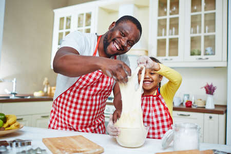 laughing girl: Happy young man and his daughter cooking pastry from dough