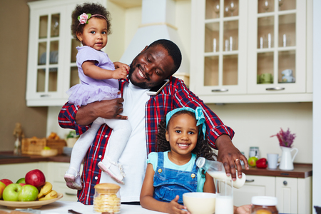 home cooking: Happy African-American man making breakfast for his daughters Stock Photo