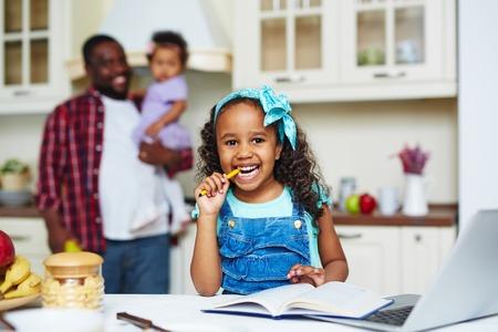 deberes: Feliz niña afroamericana mirando a la cámara en el fondo de su padre y su hermana