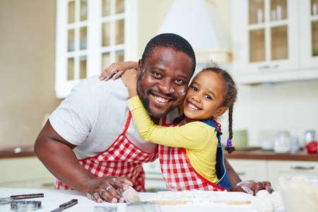 niños cocinando: Pequeña niña abrazando a su padre durante la cocción de pastelería en la cocina