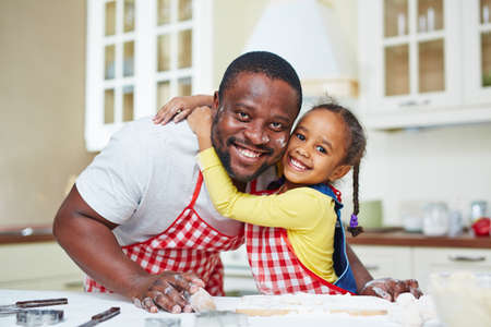 family together: Small girl embracing her father while cooking pastry in the kitchen Stock Photo