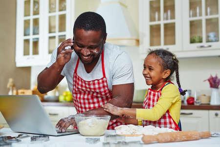 niños cocinando: Hombre joven que invita y la creación de redes en la cocina con su hija cerca Foto de archivo