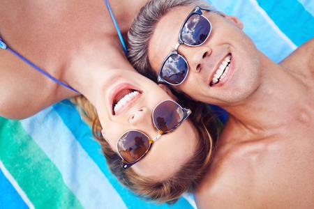 homem: Casal jovem em óculos de sol que olham a câmera, enquanto relaxa no recurso de verão Imagens