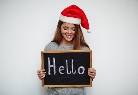 christmastide: Smiling Santa girl holding blackboard with Hello and looking at it