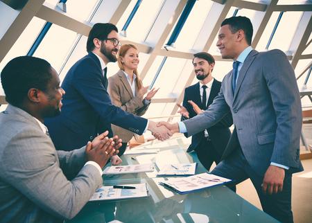 üzlet: Üzleti partnerek kézfogás aláírása után szerződést