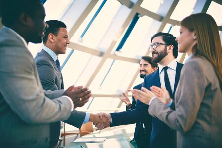 to deal with: Business partners greeting each other after signing contract