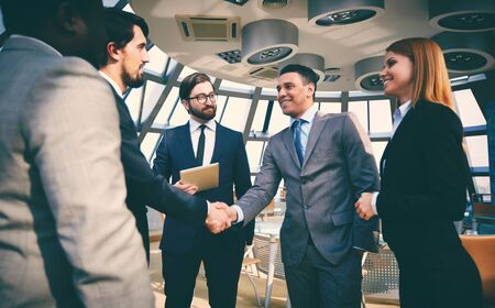 handshaking: Business partners greeting one another by handshaking Stock Photo