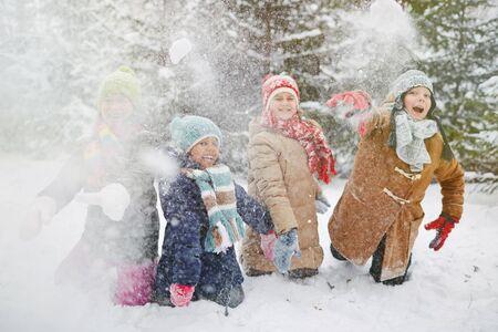 ni�os jugando: Ni�os felices en invierno llevan jugando bolas de nieve en el parque