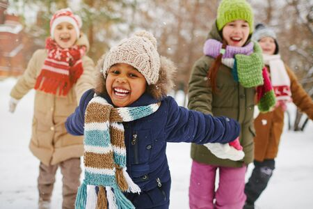 winter people: Cheerful girl and her friends spending time outdoors