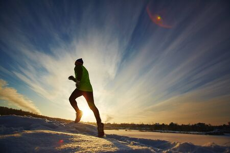 activewear: Young sportsman running in snow in rural environment