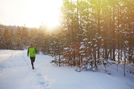 one man: Young sportsman running in the forest in winter Stock Photo