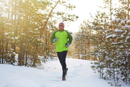 activewear: Young man in active-wear running in winter forest