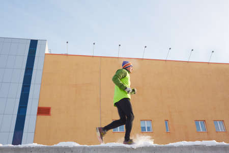 activewear: Young sportsman in active-wear running outdoors in winter