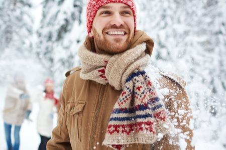winterwear: Happy guy in winterwear on background of his friends