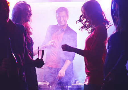 adult entertainment: Happy deejay looking at camera among dancing girls
