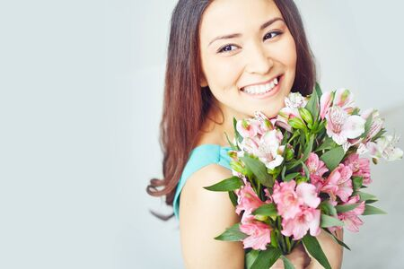축하: 꽃 꽃다발을 들고 웃는 젊은 여자