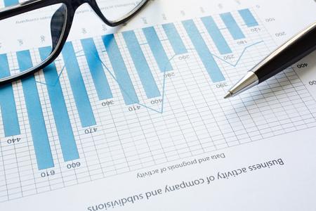 recursos financieros: Lentes y la pluma sobre el documento con los datos financieros