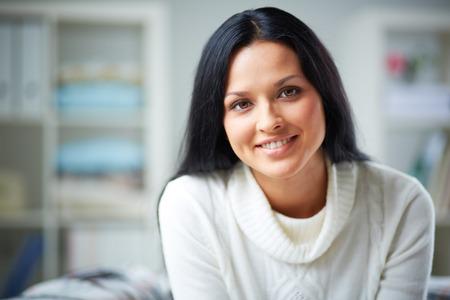 Gelukkig jonge brunette op zoek naar camera met een glimlach Stockfoto