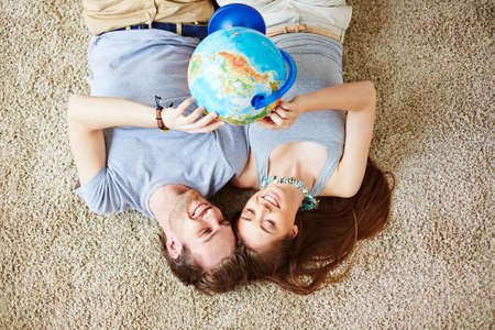restful: Restful couple with globe making plans for vacation