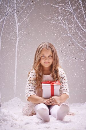 snowfall: Cute girl with gift-box sitting under snowfall