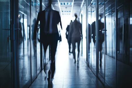 blurred people: Blurred silhouettes of business people moving in corridor