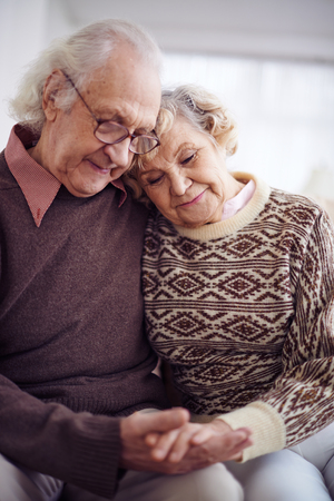 couples in love: Devoted couple of pensioners in sweaters holding by hands