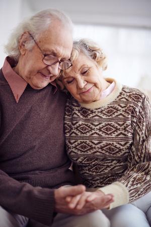 parejas amor: Pareja devota de los pensionistas en suéteres celebración por las manos Foto de archivo