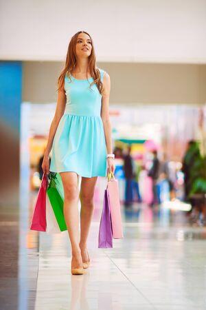 chicas de compras: Shopper bastante joven en traje azul y bolsas de papel caminando por la alameda